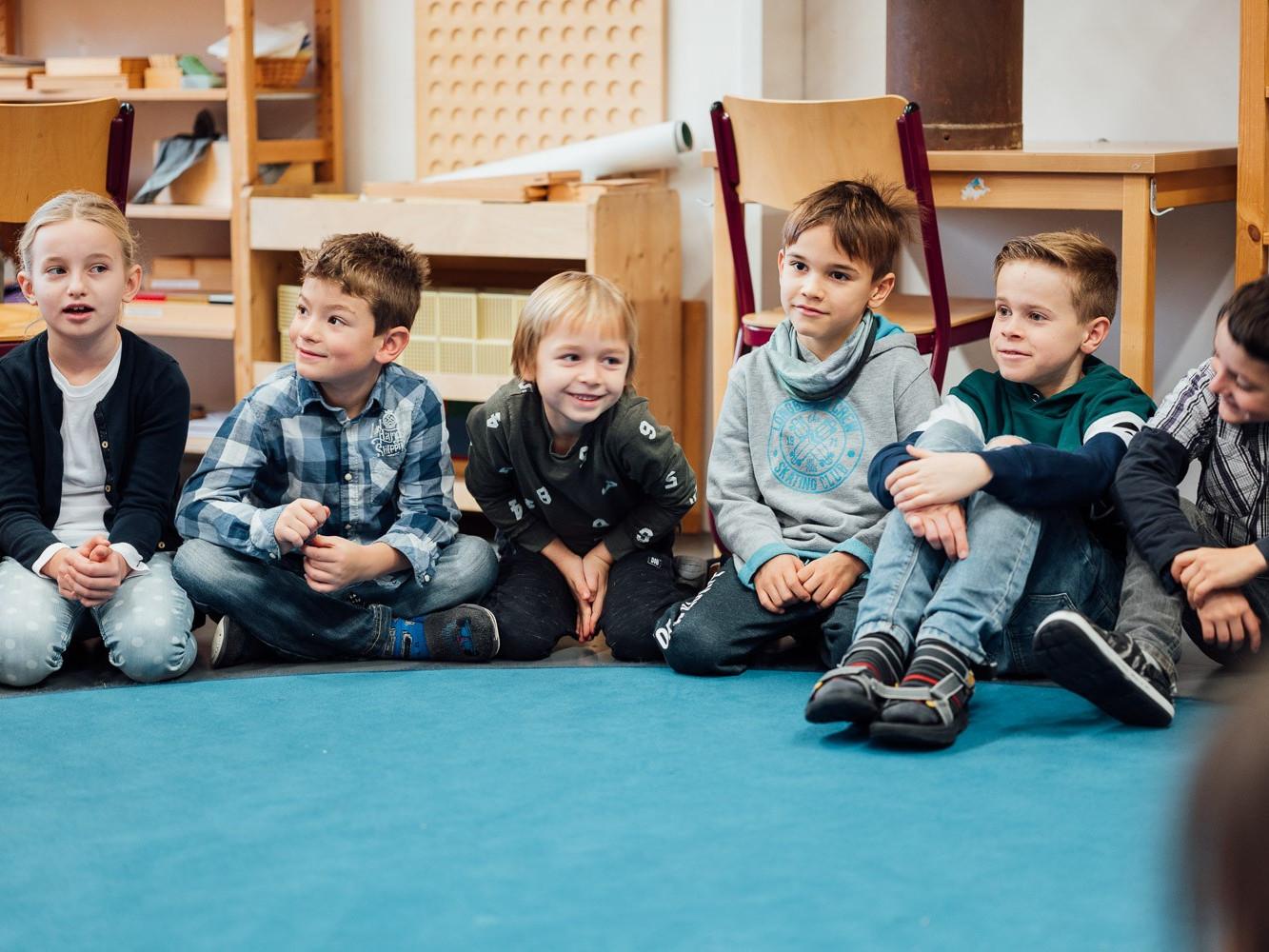 Schüler der Montessori Kaufering sitzen im Kreis