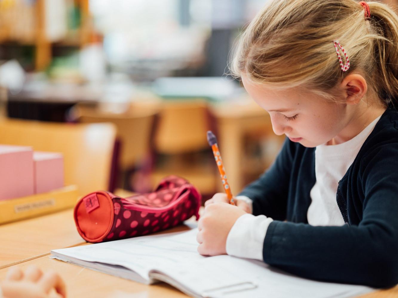 Schülerin der Montessori Kaufering schreibt in ihr Arbeitsheft